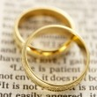 Two Wedding Rings Resting On A  Bible Page — 图库照片