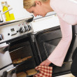 Woman Taking Cookies Out Of Oven — Stock Photo