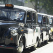 Stock Photo: London Taxis Lined Up On Sidewalk