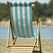 Lone Beach Chair Sitting Next To Water - Stock Photo