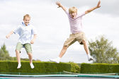 Two young boys jumping on trampoline smiling — Stock Photo