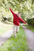 Young boy running on a path outdoors smiling — Foto Stock