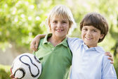 Two young boys outdoors with soccer ball smiling — Stock Photo