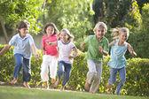Vijf jonge vrienden uitgevoerd buiten glimlachen — Stockfoto