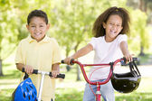 Brother and sister outdoors with scooter and bicycle smiling — 图库照片