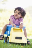 Young boy playing on toy dump truck outdoors — Stock Photo