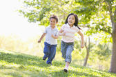 Brother and sister running outdoors smiling — Stock Photo