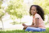 Joven sentada sonriendo al aire libre — Foto de Stock