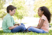 Tow young friends sitting outdoors looking at each other and smi — Stock Photo