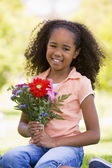 Young girl holding flowers and smiling — Stock Photo
