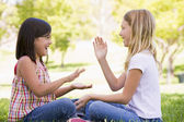 Two young girl friends sitting outdoors playing patty cake smili — Stock Photo