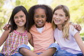 Three young girl friends sitting outdoors smiling — Stock Photo