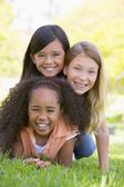 Three young girl friends piled up on top of each other outdoors — Stock Photo