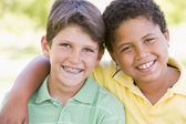 Two young male friends outdoors smiling — Stock Photo