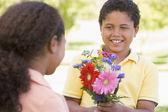 Jeune garçon donnant des fleurs de la jeune fille et souriant — Photo