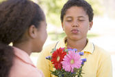 Young boy giving young girl flowers and puckering up — Stock Photo