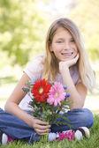 若い女の子の花を保持していると笑みを浮かべて — ストック写真