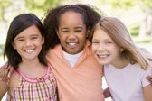 Three young girl friends outdoors smiling — Stock Photo