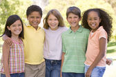 Five young friends standing outdoors smiling — Stock Photo