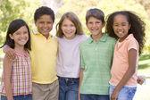 Pięć młodych przyjaciół, stojący na zewnątrz uśmiechający się — Zdjęcie stockowe