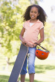 Young girl with skateboard outdoors smiling — Stock Photo