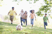 Five young friends playing soccer — Foto de Stock