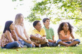 Five young friends sitting outdoors with soccer ball — Stock Photo
