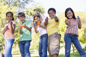 Five young friends with water guns outdoors smiling — Stock Photo