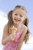 Young girl outdoors eating ice cream cone and smiling — ストック写真