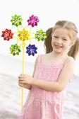Joven chica en la playa con juguete molino sonriendo — Foto de Stock
