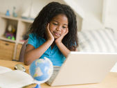 Young Girl Doing Her Homework On A Laptop — Stock Photo