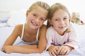 Two Young Girls In Their Pajamas Lying On A Bed — Stock Photo