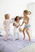 Three Young Girls Jumping On A Bed In Their Pajamas — Stock Photo