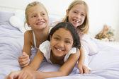 Tre unga flickor liggande på varandra i sin pyjamas — Stockfoto