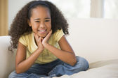 Young Girl Sitting Cross Legged On A Sofa At Home — Stock Photo