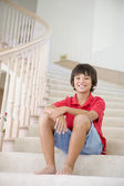 Young Boy Sitting On A Stairwell At Home — Stock Photo