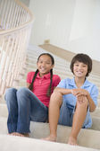 Brother And Sister Sitting On A Stairwell At Home — Stock Photo
