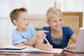Boy Pointing At Big Sisters Homework On Laptop — Foto de Stock