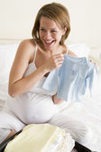 Pregnant woman packing baby clothing in suitcase smiling — Stock Photo