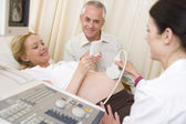 Pregnant woman getting ultrasound from doctor with husband looki — Stock Photo