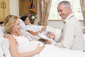 Doctor talking to pregnant woman holding chart and smiling — Stock Photo