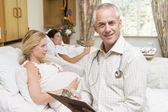 Médico sentado por mulheres grávidas, segurando o gráfico e sorrindo — Fotografia Stock