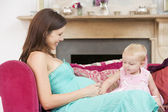 Pregnant mother with daughter in living room touching belly and — Stock Photo