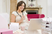 Pregnant woman in home office with laptop eating and smiling — Stock Photo