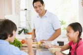 Children Having Breakfast While Dad Prepares Food — Stock Photo