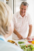 Husband Talking To Wife While Preparing meal,mealtime — Stock Photo