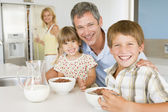 Father With Children As They Eat Breakfast And Mother In The Bac — Stock Photo