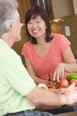 Woman Talking To Husband While Chopping Vegetables — Stock Photo