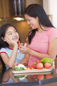 Mother Offering Daughter A Piece Of Freshly Chopped Pepper — Stock Photo