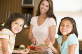 Girls Eating Pepper Strips While Mother Is Preparing meal,mealti — Stock Photo